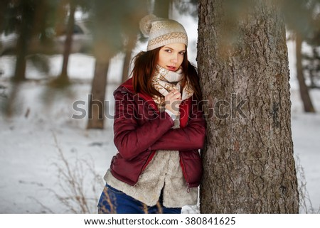 early spring portrait of cute attractive serious young girl with dark hair heat scarf and red jacket looking to camera and standing next to tree in winter forest on natural background. Outdoor - stock photo