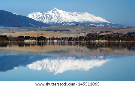 Early spring view of snowy Krivan peak (alt. 2494 meters) reflected in calm waters of Liptovska Mara. Krivan Peak is part of High Tatra Mountains and it is frequently used national symbol in Slovakia.