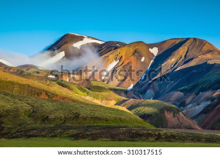 Early summer morning in the National Park Landmannalaugar, Iceland. In the hollows of rhyolitic mountain snow - stock photo