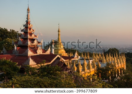 Early sunset view from Mandalay hill at Su Taung Pyai Pagoda  down to the city over illuminated Chedis - stock photo