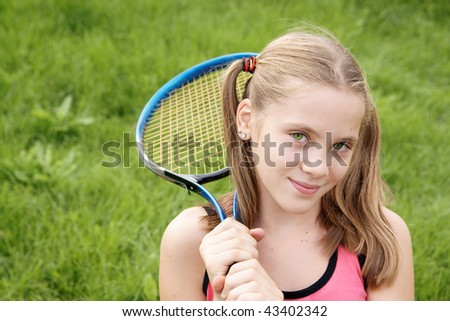 Early teenage girl in sport outfits with tennis racket on green grass background