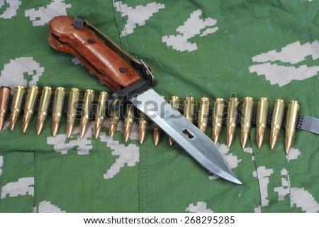 early type bayonet Kalashnikov rifle on camouflaged uniform background  - stock photo