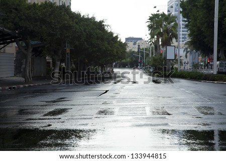 Early winter morning in Tel-Aviv, the wet street is empty from vehicles and people. - stock photo