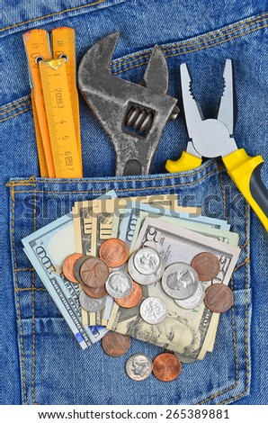 Earnings concept - money and tool in blue jeans pocket - stock photo