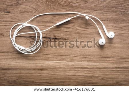 Earphone on wood background - stock photo