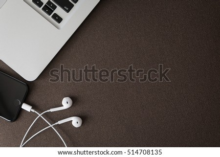 Earphone smartphone and notebook office Background.