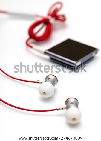 Earphones and mp3 player on a white background - stock photo