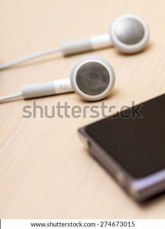 Earphones and mp3 player on the wooden table - stock photo
