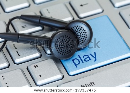 Earphones on computer keyboard with a play button - stock photo