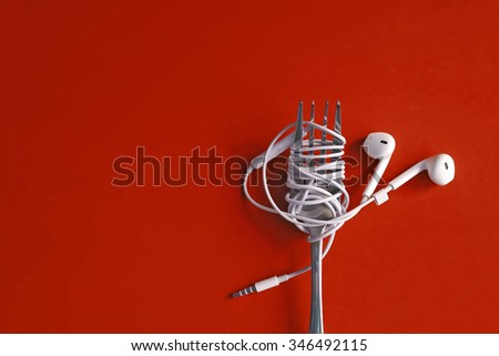 Earphones on fork on red background. Concept of Music. - stock photo
