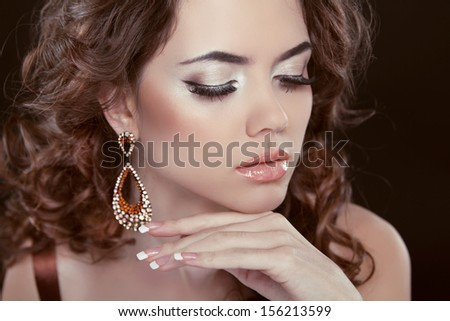 Earrings. Beauty Woman With Long Brown Curly Hair. Hairstyle. Beautiful Model Girl Portrait. Accessory - stock photo
