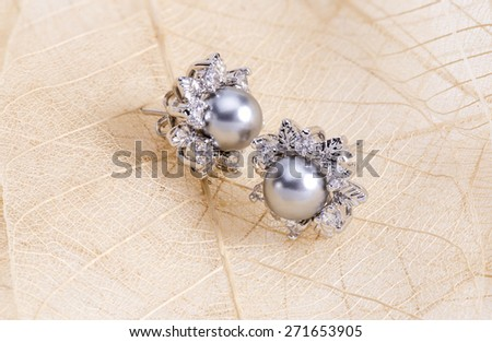Earrings in the shape of the pearls on leaf fiber. - stock photo