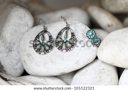 Earrings with blue gemstones for bridesmaids displayed on white stones. - stock photo