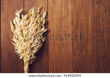 ears of oat on wooden background - stock photo