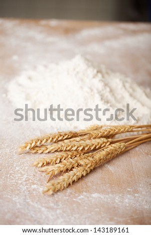 Ears of ripe golden wheat lying on a counter in a bakery together with sprinkled flour - stock photo