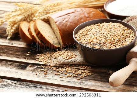 Ears of wheat and bowl of flour and wheat grains on brown wooden background - stock photo