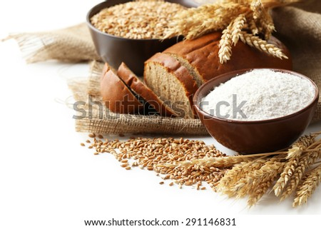 Ears of wheat and bowl of flour and wheat grains on white background - stock photo