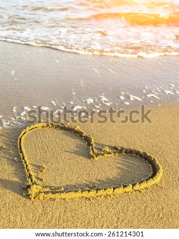 eart drawn in sea beach sand, soft wave in a sunny day. - stock photo