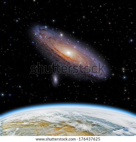 Earth and Andromeda galaxy on a dark starry background. Earth disk furnished by NASA/JPL. - stock photo