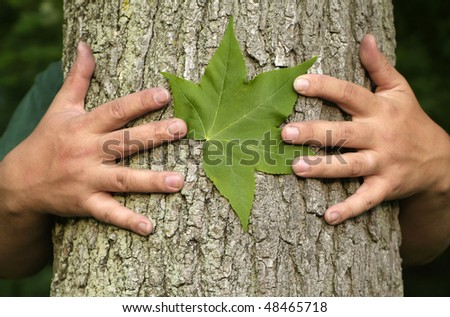 Earth Day Concept: Eco minded person hugging a tree with a green leaf between their hands. - stock photo