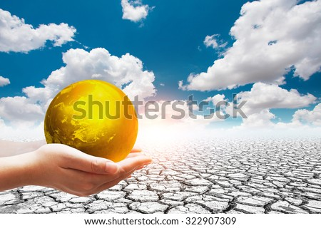 Earth day concept .Two Hand holding the Golden world ball on the soil cracked.Elements of this image furnished by NASA - stock photo