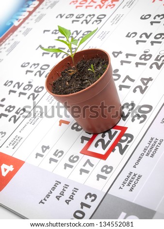 Earth day marked on the calendar with a young plant as a symbol. - stock photo