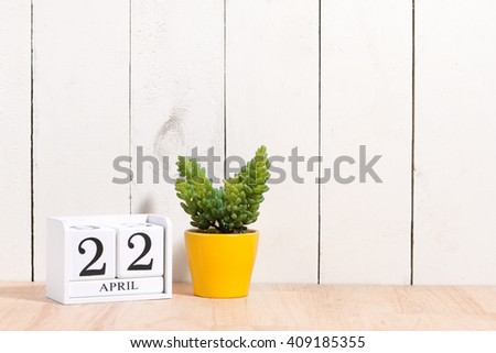 Earth Day, save the date white block calendar, April 22, with ornamental plants in flowerpots against a white wooden background. - stock photo