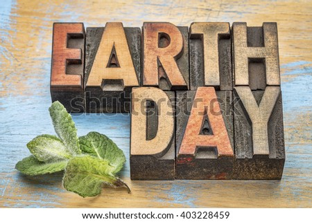 earth day - word abstract in vintage letterpress wood type with a green peppermint leaf - stock photo
