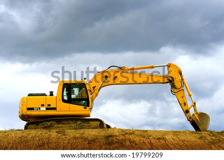 Earth digger on a dramatic cloudy day - stock photo