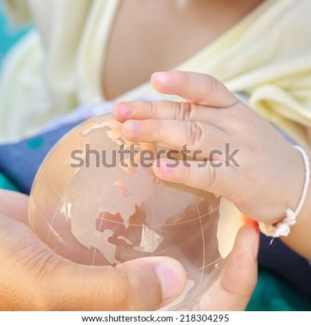 Earth glass globe in hand - stock photo