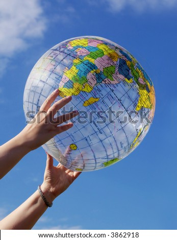 Earth globe, hands and blue sky - stock photo