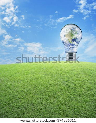 Earth globe in light bulb with green grass field over blue sky, Energy conservation and environmental concept, Elements of this image furnished by NASA