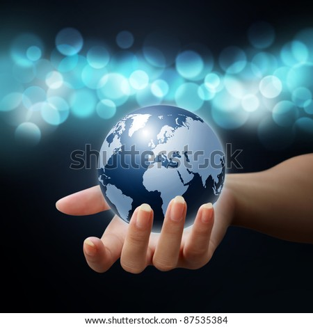 earth globe in woman hands on blue bokeh background