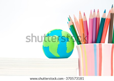 Earth globe made of clay on books stack and color pencil in colorful cup. Environmental awareness and education concept. Earth day holiday concept - stock photo