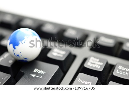 Earth globe over keyboards - stock photo