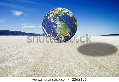 Earth image hovering over a dry playa representing the planet's rush towards a global drought and severe water shortage.  Earth image courtesy of NASA. - stock photo