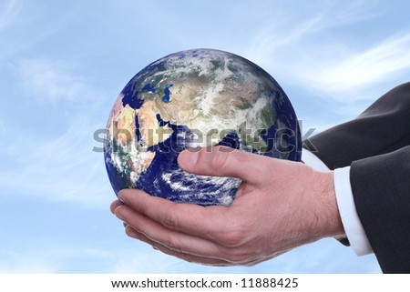 earth in a hands on background blue sky - stock photo