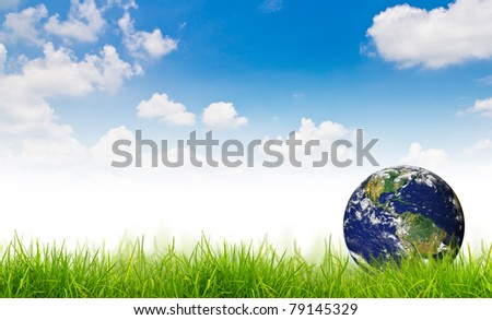 Earth in Fresh spring green grass - stock photo