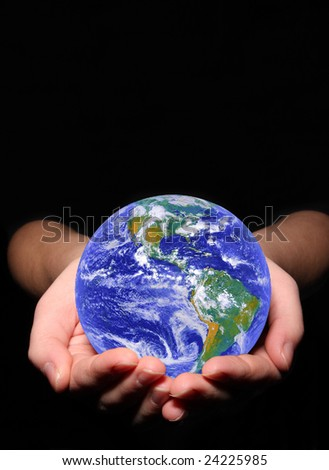 earth in woman hands on black background - stock photo