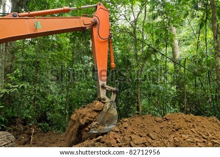 earth mover in tropical rainforest, forest destruction - stock photo
