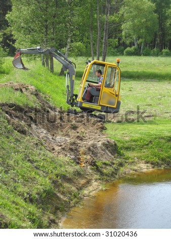 Earth mowing near the pond with small excavator - stock photo