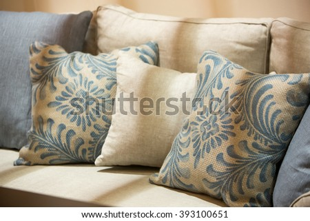 Earth tone color pillows and cushion on a luxury  style fabric sofa under shade with soft sunlight cast on the sofa. - stock photo