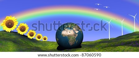 Earth under a rainbow and on a hill made of green grass and surrounded by sunflowers, wind turbines and birds - stock photo