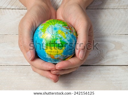 Earth with female Hands on wooden background - stock photo