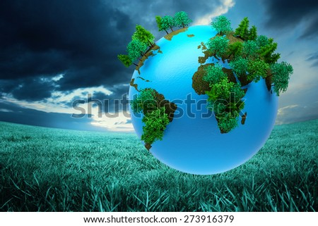 Earth with forest against blue sky over green field - stock photo