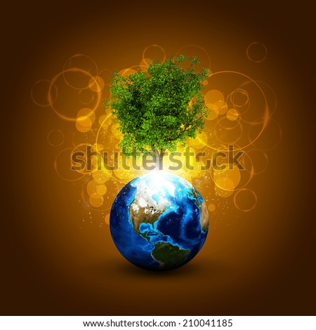Earth with magical green tree and rays of light - stock photo