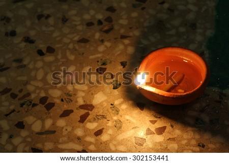 earthen lamp - diya on floor removes the darkness and  spread illumination - stock photo
