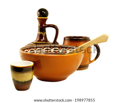 Earthenware soup-plate, cup and a wooden spoon on a white background - stock photo