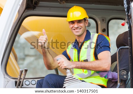 earthmover operator giving thumb up on construction site - stock photo