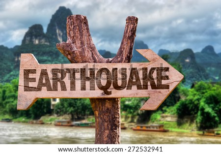Earthquake wooden sign with countryside background - stock photo